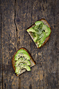 Slice of toasted bread with acocado, cress and hemp seeds on wood - LVF004424