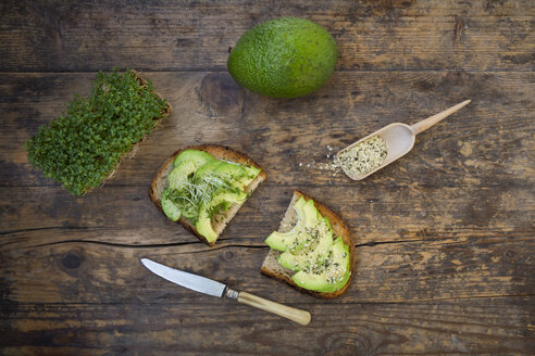 Slice of toasted bread with acocado, cress and hemp seeds on wood - LVF004427