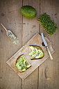 Slice of toasted bread with acocado, cress and hemp seeds on wooden board - LVF004433