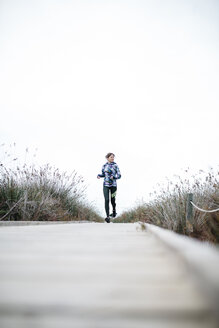 Spain, Tarragona. Woman running on a wooden boardwalk - JRFF000333