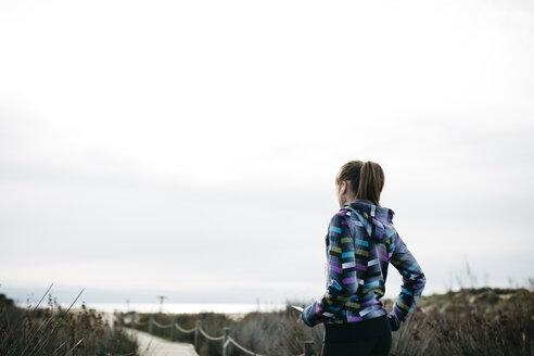 Spain, Tarragona, Woman ready to start running on a wooden footbridge - JRFF000336