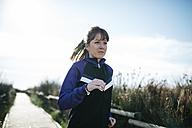 Spain, Tarragona, Woman running on a wooden boardwalk - JRFF000342