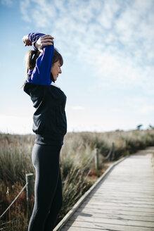 Spain, Tarragona, Woman doing stretching before running - JRFF000345