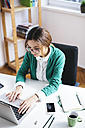 Young businesswoman working at desk in the office - AKNF000030