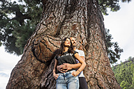 Spain, Tenerife, couple in love standing in front of a giant tree at Teide National Park - SIPF000066