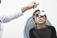 Optometrist examining eyesight of boy - ERLF000102