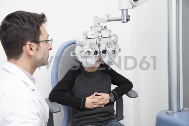 Optometrist examining eyesight of boy - ERLF000108