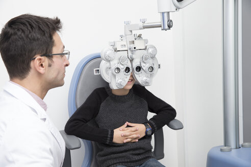 Optometrist examining eyesight of boy - ERLF000108