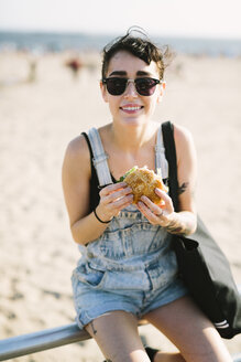 USA, New York, Coney Island, young woman eating a hamburger at the beach - GIOF000628