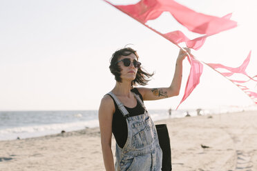 USA, New York, Coney Island, young woman holding red flags on the beach - GIOF000655
