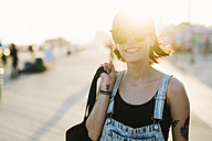 USA, New York, Coney Island, smiling young woman on boardwalk at sunset - GIOF000658