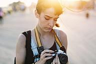 USA, New York, Coney Island, young woman looking at camera at sunset - GIOF000667
