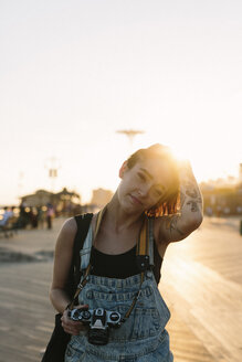 USA, New York, Coney Island, young woman with camera at sunset - GIOF000670