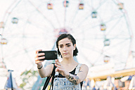 USA, New York, Coney Island, young woman taking a selfie at the amusement park - GIOF000676