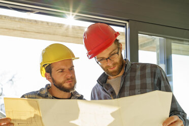 Two craftsmen looking at building plan in construction site - LAF001591