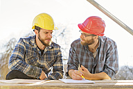 Two craftsmen discussing and taking notes in construction site - LAF001594