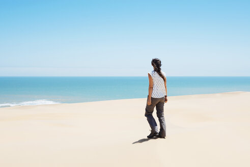 Namibia, Namib desert, Swakopmund, woman walking among the dunes of the desert to the sea - GEMF000630