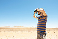 Namibia, Namib desert, man with hat using binoculars to look away - GEMF000645