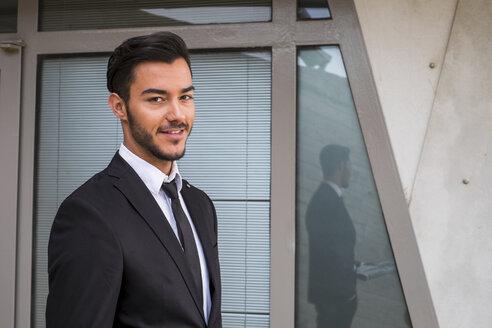 Portrait of smiling businessman wearing black suit - SIPF000083