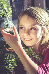 Portrait of smiling girl decorating Christmas tree - SARF002463