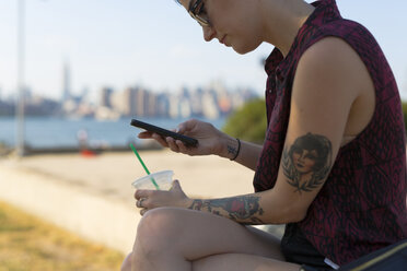 USA, New York City, Brooklyn, tattooed woman sitting on a bench looking at her smartphone - GIOF000687