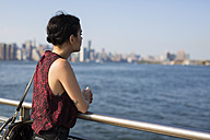 USA, New York City, Williamsburg,  young woman leaning on a railing - GIOF000693