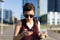 Portrait of young woman looking at her smartphone - GIOF000699