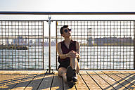 USA, New York City, Williamsburg, portrait of tattooed young woman leaning against railing - GIOF000702