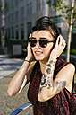Portrait of tattooed young woman with headphones and sunglasses - GIOF000705