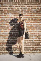 Portrait of young woman leaning against brick wall - GIOF000711