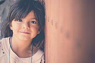 Portrait of smiling girl leaning against wall - SIPF000103