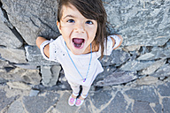 Portrait of little girl with mouth open in front of a rock face - SIPF000106