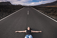Spain, Tenerife, woman lying on an empty road with outstretched arms - SIPF000114