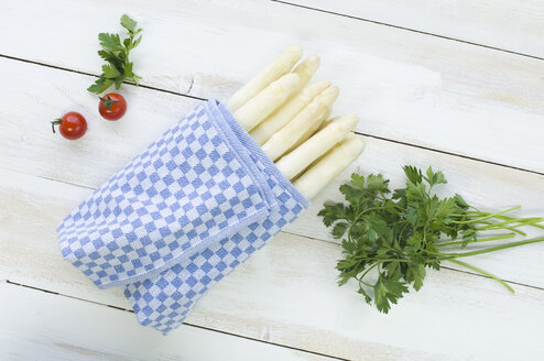Bunch of white asparagus wrapped in kitchen towel, parsley and cherry tomatoes on wood - ASF005808