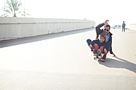 Spain, Catalonia, Barcelona, Uncle and kids doing skate board - VABF000064