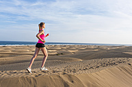 Young woman jogging on the beach - DIGF000002