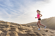 Young woman jogging on the beach - DIGF000008