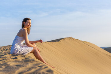 Woman sitting on dune, contemplating - DIGF000014