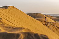 Woman walking over sand dunes - DIGF000020