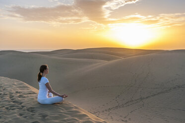 Woman practising yoga on sand dunes - DIGF000026