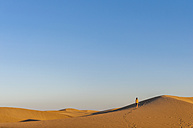 Woman walking over sand dunes - DIGF000032