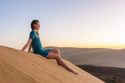 Woman sitting on dune, contemplating - DIGF000035