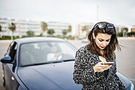 Spain, Cubelles, young woman sitting on the hood of the car looking at her smartphone - JRFF000352