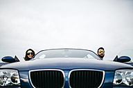 Young couple taking the heads of their car - JRFF000355