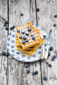 Stack of waffles with icing sugar and blueberries on plate - LVF004454