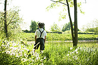 Italy, back view of little boy wearing vintage clothing enjoying nature - SIPF000120
