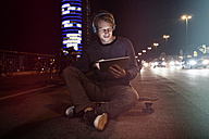Germany, Munich, man with headphones sitting on his skateboard using digital tablet at night - RBF004073