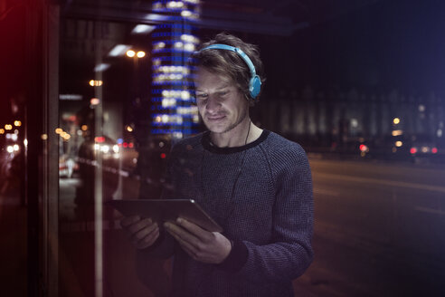 Germany, Munich, man with headphones standing at bus stop using digital tablet at night - RBF004076