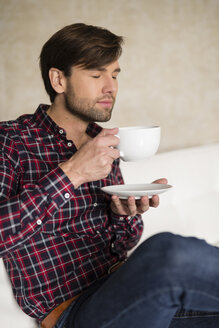 Portrait of man with closed eyes sitting on couch holding a cup of coffee - SHKF000467