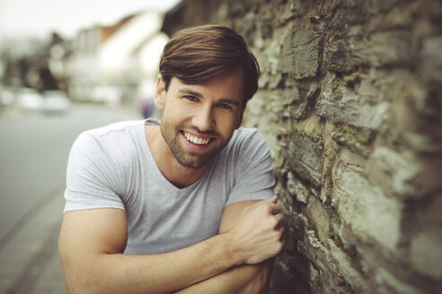 Portrait of smiling man wearing t-shirt leaning against stone wall - SHKF000470